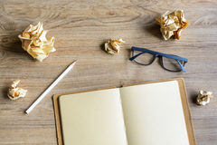 Crumpled paper balls with eye glasses and notebook on wood desk Stock Image