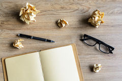 Crumpled paper balls with eye glasses and notebook on wood desk Stock Images