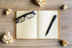 Crumpled paper balls with eye glasses and notebook on wood desk Royalty Free Stock Images