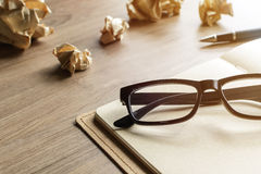 Crumpled paper balls with eye glasses and notebook on wood desk Stock Photos