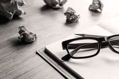 Crumpled paper balls with eye glasses and notebook on wood desk Stock Photo