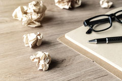 Crumpled paper balls with eye glasses and notebook on wooden des Stock Images