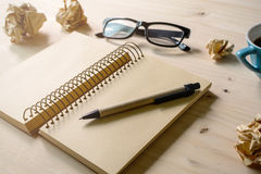 Crumpled paper balls with eye glasses, pen and notebook Stock Photo