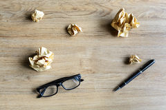 Crumpled paper balls with eye glasses and pen on wood desk Stock Images