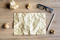 Crumpled paper balls with eye glasses on wood desk Stock Photos