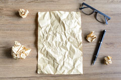 Crumpled paper balls with eye glasses on wood desk Royalty Free Stock Photos