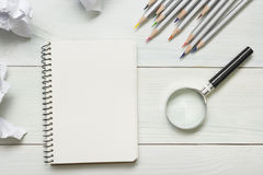 Crumpled paper balls, magnifying glass, pencils and notebook with blank white sheet  on wooden table. Creativity crisis Stock Photo