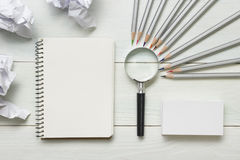 Crumpled paper balls, magnifying glass, pencils and notebook with blank white sheet  on wooden table. Creativity crisis Royalty Free Stock Photo