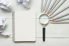 Crumpled paper balls, magnifying glass, pencils and notebook with blank white sheet  on wooden table. Creativity crisis Royalty Free Stock Photos