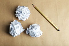 Crumpled paper balls with pencil on brown background. Royalty Free Stock Images