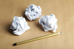 Crumpled paper balls with pencil on brown background. Stock Image