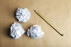 Crumpled paper balls with pencil on brown background. Royalty Free Stock Photo