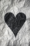 Crumpled paper with black heart Stock Image