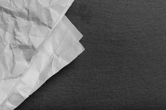 Crumpled paper on black slate cutting board Royalty Free Stock Image