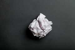 Crumpled paper on black slate cutting board Royalty Free Stock Photography