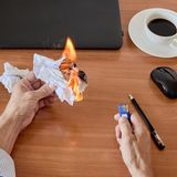 Crumpled paper burning. Crumpled sheets of waste paper burning on office table royalty free stock photo
