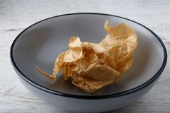Crumpled paper in empty bowl. Crumpled brown paper in empty gray bowl royalty free stock image