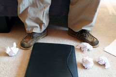 Crumpled Paper on Floor. Man sitting in chair with crumpled paper thrown on the floor Royalty Free Stock Images