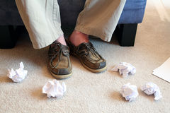 Crumpled Paper on Floor. Man sitting in chair with crumpled paper thrown on the floor Royalty Free Stock Image