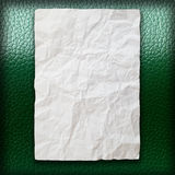 Crumpled paper on green leatherette. Background Royalty Free Stock Image