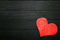 Crumpled paper heart. On black wooden table royalty free stock image