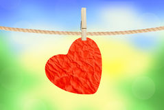 Crumpled paper heart hanging on rope over nature background Stock Photography