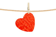 Crumpled paper heart hanging on rope on white background Stock Images