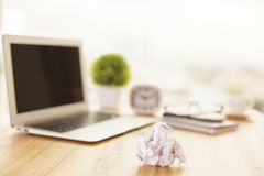 Crumpled paper on office desk. Piece of crumpled paper on wooden office desk with blurry laptop, plant, clock, glasses, coffee and stationery items. Mock up royalty free stock photos