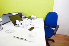 Crumpled paper over laptop on desk with empty chair and folders Royalty Free Stock Photos
