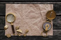 Crumpled paper page, compass, gold and magnifying glass. Blank crumpled page with copy space for treasure map, compass, magnifying glass and golden nuggets on Stock Photos