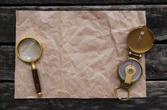 Crumpled paper page, compass and magnifying glass. Blank crumpled paper page with copy space for treasure map for example, compass and magnifying glass Royalty Free Stock Photography