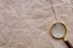 Crumpled paper page and magnifying glass. Blank crumpled paper page and magnifying glass.  Seaching, discovering, revealing and exploring concept background Royalty Free Stock Photo