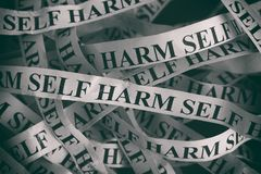 Crumpled paper pieces with words Self Harm Stock Photo