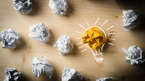 Crumpled paper symbolizing different solutions with one highlighted. As a light bulb as the right one Royalty Free Stock Images