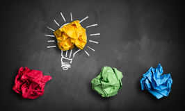 Crumpled paper symbolizing different solutions. With one highlighted as a light bulb as the right one Stock Photo