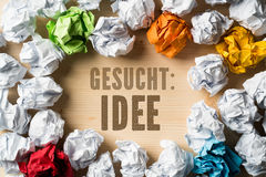 Crumpled paper symbolizing different solutions and the phrase `Wanted: IDEA`. In German Stock Image