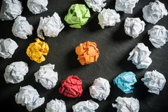Crumpled paper symbolizing different solutions with some standing out stock images