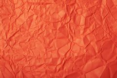 Crumpled paper texture. Close-up fragment of a red crumpled paper texture as a backdrop composition stock image