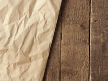 Crumpled paper on wood. Crumpled paper on an old wooden table using as natural background with space for text or image Stock Images