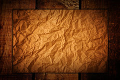 Crumpled paper on wood Stock Images