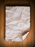 Crumpled paper on wood wall Stock Images