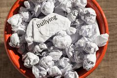 Crumpled paper written bullying inside the trash can. Paper ball stock photos