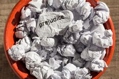 Crumpled paper written prejudice inside the trash can. Paper bal. Ls. Old and abandoned idea or practice. Macro photography Royalty Free Stock Images