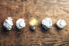Crumpled papers with light bulb on wooden background. Idea stock photos