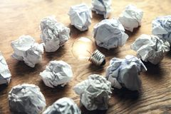 Crumpled papers with light bulb on wooden background. Idea stock images