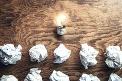Crumpled papers with light bulb on wooden background. Idea stock photo