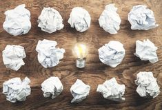 Crumpled papers and light bulb on wooden table. Great Idea stock photo