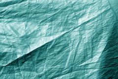 Crumpled plastic textile texture in cyan tone. Abstract background and texture for design stock photos