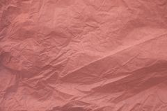 Crumpled recycled pink paper texture and background for design. Close up view of abstract wrinkled pink texture. Crumpled recycled pink paper texture and stock image