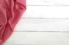 The Crumpled red checkered tablecloth or napkin on empty white w. Crumpled red checkered tablecloth or napkin on empty white wooden table with copy space for Royalty Free Stock Photography